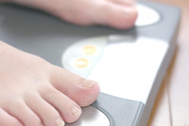 体重計で体重を量っている女性
